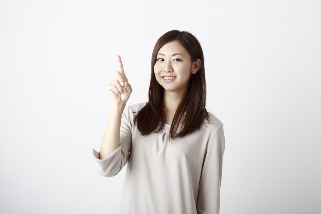 1の数字を指で作る女性